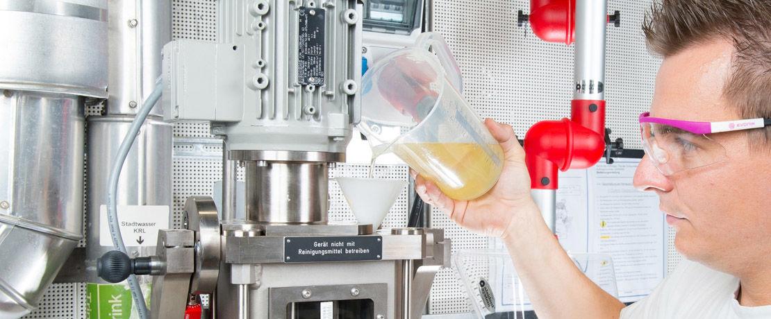 technician pouring liquid into lab machine