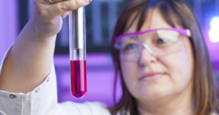 scientist looking at vial of liquid