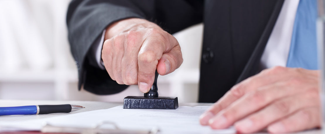 man stamping a piece of paper