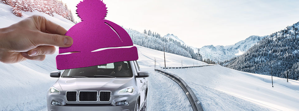 Car with winter hat driving on snowy road