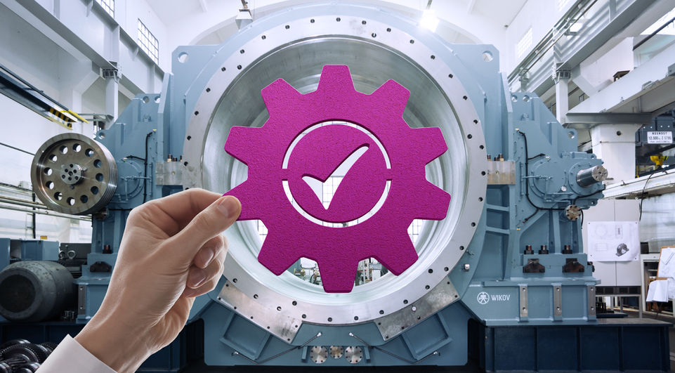 Symbol of a gear with check mark held up to industrial equipment