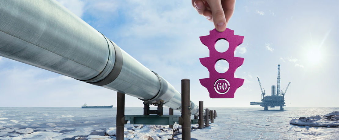 pipeline on the sea with ice and a purple traffic light