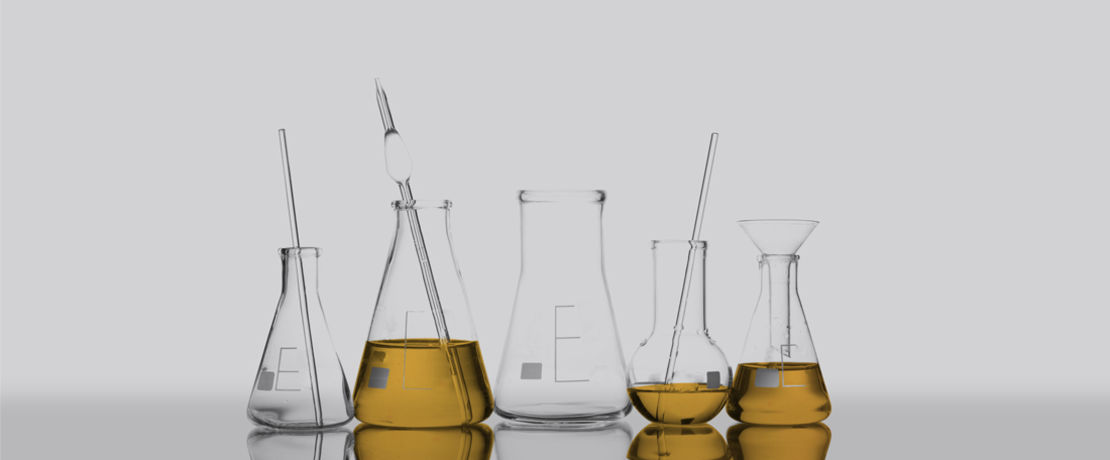 five beakers and three of them filled with oil