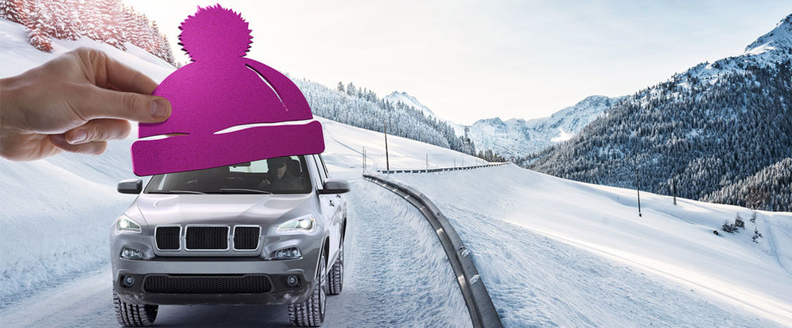 car driving in the snow in the mountains with a purple hat on